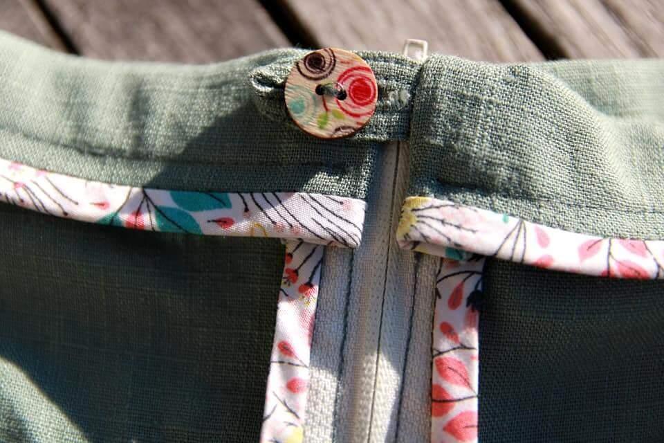 Knopf und Riegel mit Schrägband versäuberter Bund